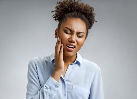 Woman suffering from annoying strong teeth pain. Photo of african american woman in blue shirt on gray background. Medical concept.