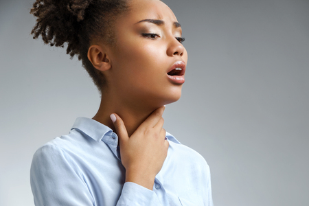 Throat pain. Woman holding her inflamed throat. Photo of african american woman in blue shirt on gray background. Medical concept Stockfoto - 112143579