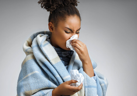 Sick woman sneezing and blowing nose. Photo of african american woman wrapped in paid on gray background. Medical concept Stock Photo
