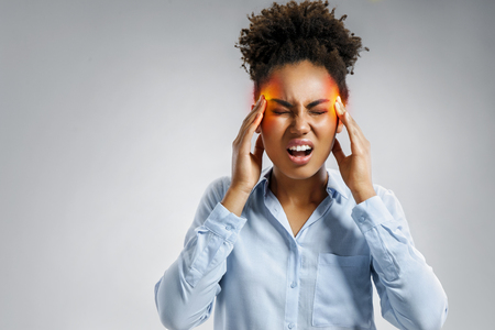 Woman with pain in her temples. Photo of african american woman in blue shirt suffering from stress or a headache grimacing in pain on gray background. Medical concept.