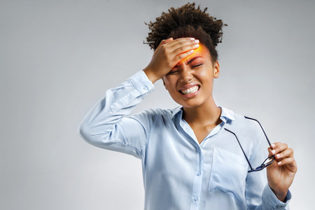 Tired girl suffering from painful headache and stress. Photo of african american woman in blue shirt holding hand on forehead on gray background. Medical concept
