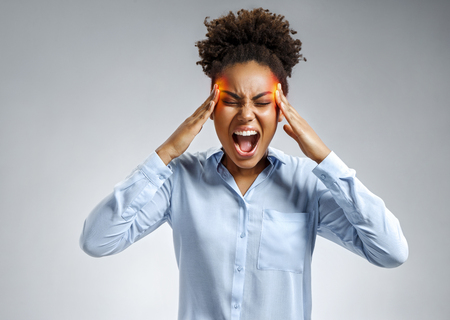 Woman suffering from stress or a headache grimacing in pain. Photo of african american woman in blue shirt on gray background. Medical concept. Stock Photo - 112507089