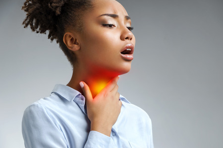 Throat pain. Woman holding her inflamed throat. Photo of afrikan amerikan woman in blue shirt on gray background. Medical concept.