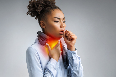 Kranke Frau mit Halsschmerzen. Foto einer afroamerikanischen Frau im blauen Hemd, die an einem Grippevirus auf grauem Hintergrund leidet. Medizinisches Konzept. Standard-Bild