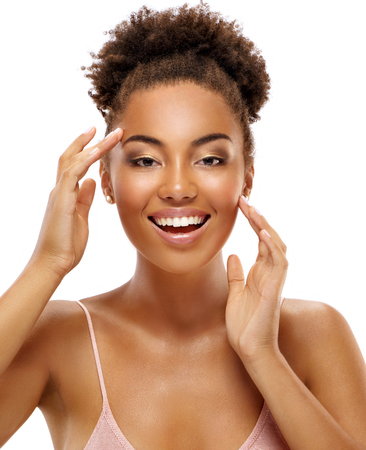 Happy young girl touching her face. Photo of smiling african american girl with perfect skin isolated on white background. Beauty & Skin care concept