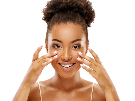 Attractive woman doing facial massage. Photo of african american woman with clean healthy skin on white background. Skin care and beauty concept Reklamní fotografie