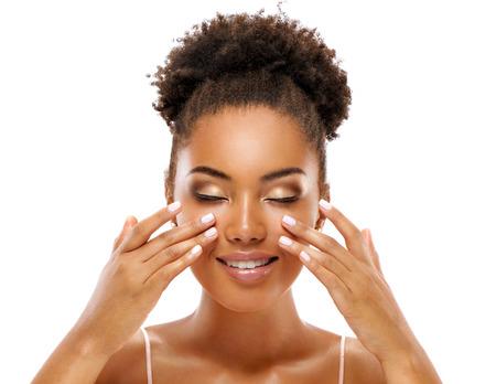Schöne Frau, die Gesichtsmassage tut und ihr Gesicht berührt. Foto der afrikanischen Frau mit sauberer gesunder Haut auf weißem Hintergrund. Hautpflege- und Schönheitskonzept
