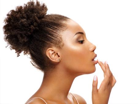 Bella donna di profilo che si tocca le labbra. La foto della donna africana finisce il trucco su fondo bianco. Concetto di giovinezza e cura della pelle Archivio Fotografico