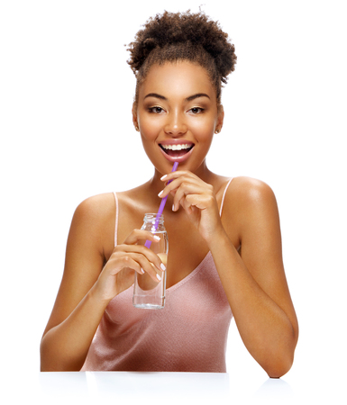 Smiling beautiful woman drinks clean water. Photo of young african american woman isolated on white background. Youth and Beauty Reklamní fotografie
