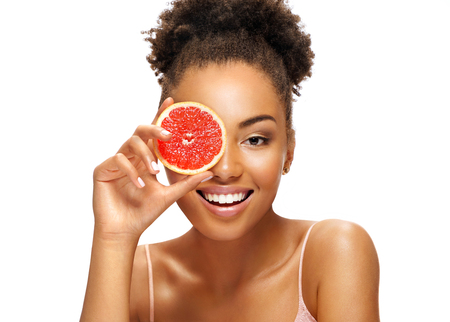 Charming young girl holding a slice of pomelo in front of her face. Photo of smiling african american woman isolated on white background. Beauty & Skin care concept Reklamní fotografie