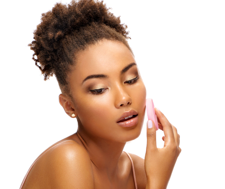 Beautiful girl applying foundation on her face using makeup sponge. Photo of african american girl on white background. Skin care and beauty Reklamní fotografie