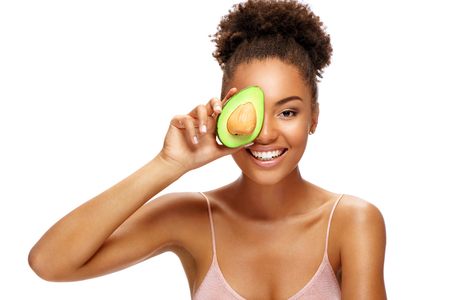 Pretty young woman holding half an avocado in front of her face. Photo of smiling african woman isolated on white background. Beauty & Skin care concept