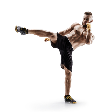 Athletic man practicing tae-bo exercises, kicking forward with legs. Photo of sporty muscular male in sports clothes over white background
