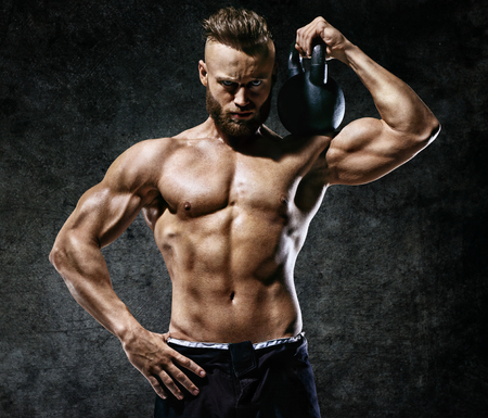 Sporty man working out with a kettlebell. Photo of muscular man on dark background. Strength and motivation