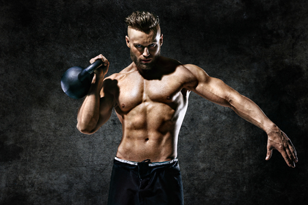 Sporty man working out with a kettlebell. Photo of man on dark background. Strength and motivation 스톡 콘텐츠