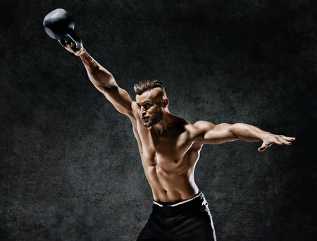 Young muscular guy training with kettlebell. Photo of handsome man with naked torso on dark background. Strength and motivation