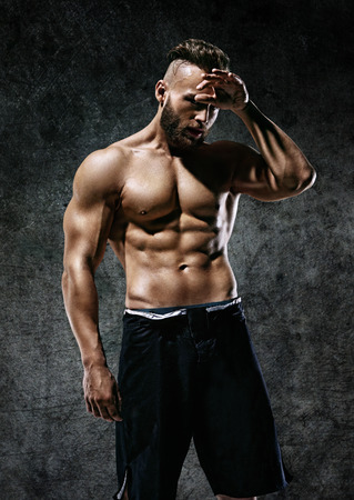 Tired sporty man. Photo of strong man with naked torso on dark background. Strength and motivation.