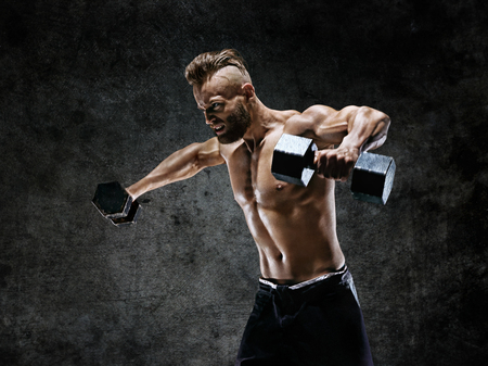 Bodybuilder doing the exercises with dumbbells. Photo of young man with naked torso on dark background. Strength and motivation. Reklamní fotografie