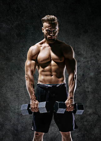 Young guy working out with dumbbells. Photo of strong male with naked torso on dark background. Strength and motivation