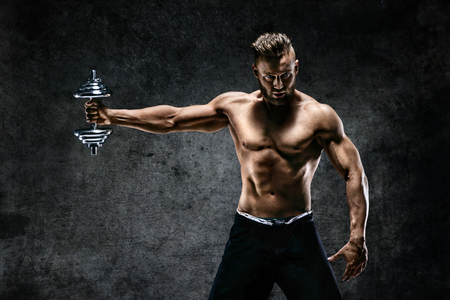 Young male bodybuilder doing exercise with heavy weight dumbbells. Photo of muscular man on dark background. Strength and motivation.