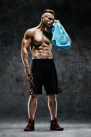 Resting time. Man with skipping rope and towel in his hands. Photo of sporty muscular man on dark background. Health concept.