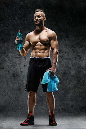 Sporty man having a break. Photo of muscular man with water and towel in his hands on dark background. Health concept. Reklamní fotografie