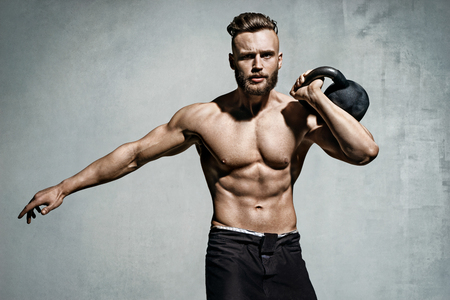 Young muscular man training with kettlebells. Photo of man with naked torso on grey background. Strength and motivation