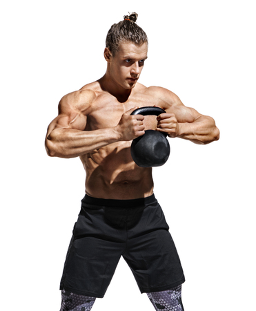 Sporty man training with kettlebell. Photo of athletic man with naked torso and perfect physique on white background. Strength and motivation Reklamní fotografie