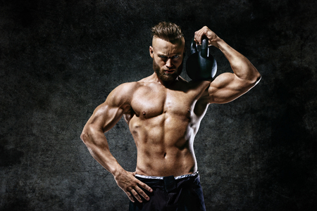 Athletic man working out with a kettlebell. Photo of man on dark background. Strength and motivation