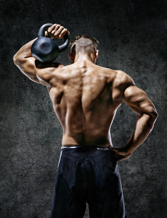Muscular back of man. Rear view of fitness model with kettlebell on dark background. Strength and motivation Reklamní fotografie