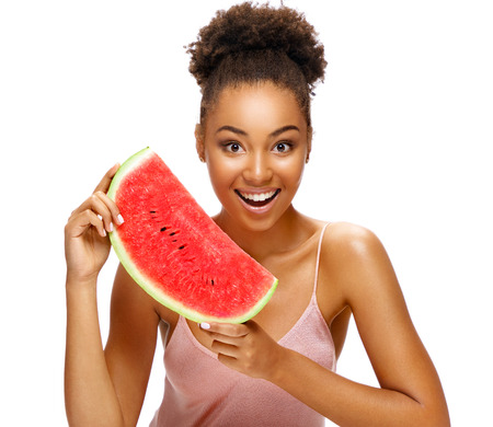 Happy girl holding red ripe watermelon slice. Portrait of smiling african american girl isolated on white background. Detox concept Reklamní fotografie