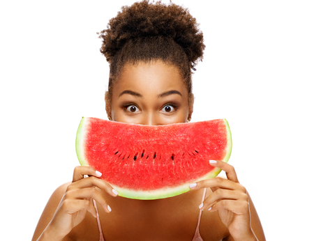 Pretty young girl holding slice of watermelon in front of her face. Portrait of smiling african american girl isolated on white background. Healthy & Happy