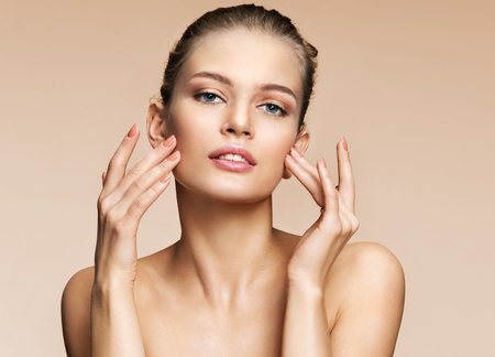 Woman doing facial massage, touching her face. Photo of woman with clean healthy skin on beige background. Skin care and beauty concept