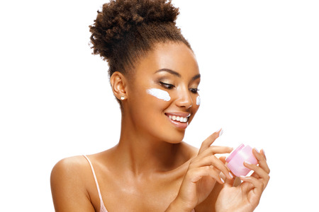 Аttractive girl using moisturizing cream. Photo of smiling african american girl on white background. Beauty & Skin care concept