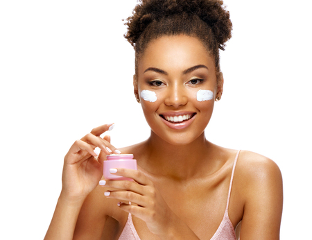 Beautiful woman using moisturizing cream. Photo of smiling african american woman on white background. Skin care and beauty concept Stock Photo