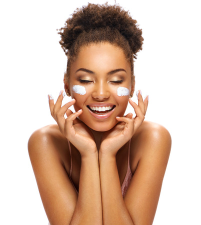 Happy young girl with moisturizing cream on her face. Photo of smiling african american girl isolated on white background. Skin care and beauty concept Banque d'images - 113555840