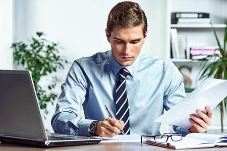 Pracownik siedzi przy biurku i sprawdza dokumenty. Zdjęcie udanego człowieka pracującego w biurze. Pomysł na biznes