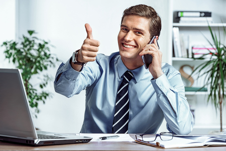 Cheerful businessman talking on the phone and showing thumb up. Photo of successful man working in the office. Business concept