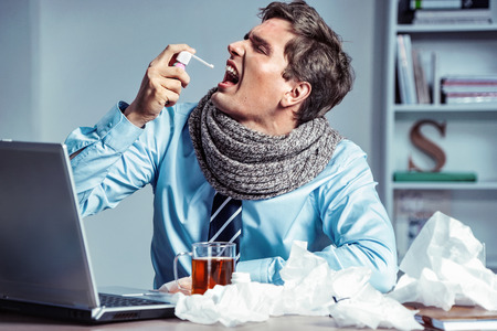 Sick employee using spray for throat. Photo of young man in office suffering virus of flu. Medical concept. Stock Photo