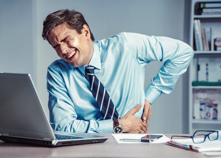 Employee suffers from severe pain in back. Photo of man working in the office. Medical concept. Zdjęcie Seryjne