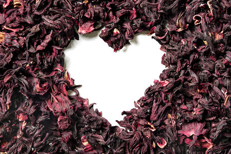 Heart shaped of dry hibiscus petals on white background. Karkade, red tea. Top view. Close up. High resolution