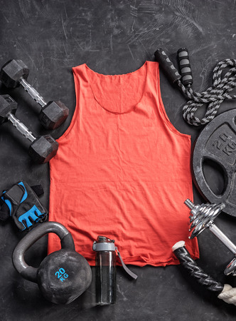 Red t-shirt and sports equipment on a black background. Top view. Motivation. Copy space