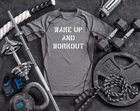 Grey t-shirt and sports equipment on a black background. Top view. Motivation. Copy space Reklamní fotografie