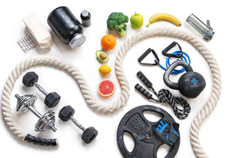 Sports equipment and healthy nutrition on a white background. Top view. Motivation