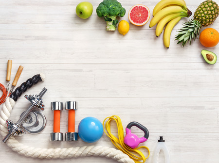 Sports equipment and healthy food on a white wooden background. Top view. Motivation