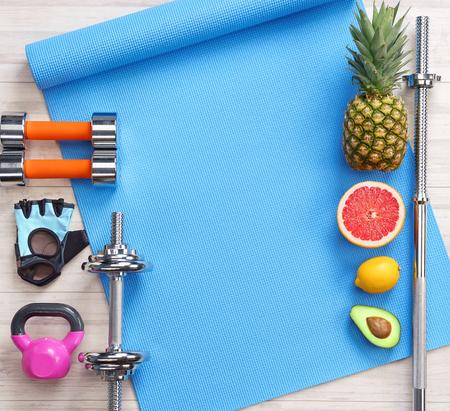 Sportgeräte und gesundes Essen auf weißem Holzhintergrund. Ansicht von oben. Motivation