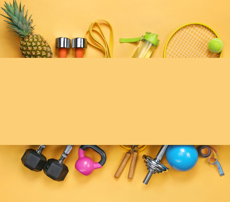 Sports equipment and organic food on yellow background. Top view. Motivation