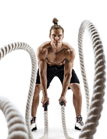 Handsome strong man working out with heavy ropes. Photo of man in sportswear isolated on white background. Cross fit. Full length Reklamní fotografie