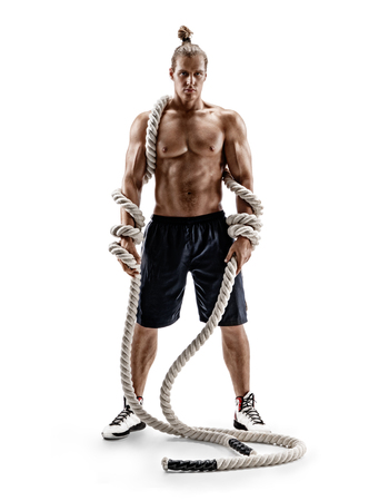 Athletic strong man with heavy ropes in hands. Photo of muscular male with naked torso isolated on white background. Full length Reklamní fotografie