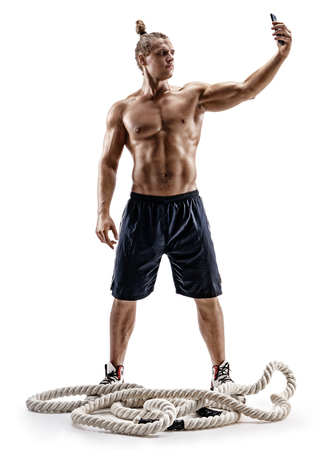Strong man taking selfie on smartphone after workout. Photo of man with naked torso isolated on white background. Strength and motivation. Full length
